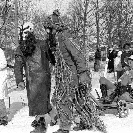 Fašiangovníci v maskách ťahajú vozík s maskovaným mužom. Čilistov. © Tibor Szabó, 1985