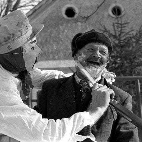 Muž v maske holí náhodného diváka fašiangových obchôdzok. Čilistov. © Tibor Szabó, 1985