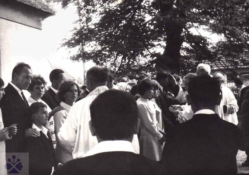 Birmovní (é) otcovia (matky) s birmovanými deťmi v rade vľavo pri udeľovaní svätého birmovania biskupom pred kostolom v obci. Lozorno 1969. Súkromný archív Ľ. Falťanovej