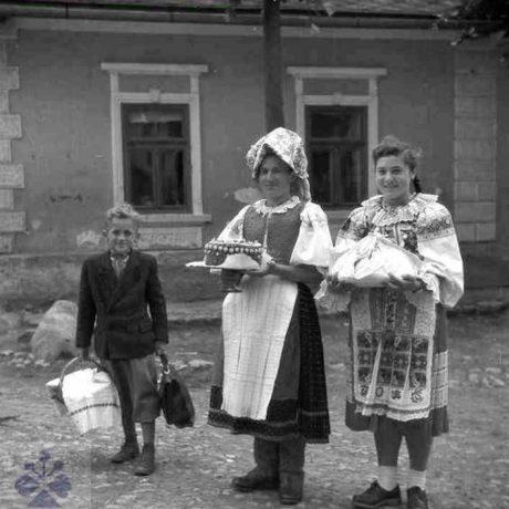 Žena s dievčaťom idúce na svadbu nesú tortu a koláče ako dary. Pohorelá (okr. Brezno), 1954. Archív negatívov Ústavu etnológie SAV v Bratislave. Foto: J. Pátková