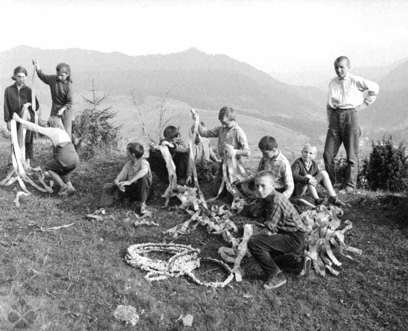 Príprava stužiek a pletených kvetinových vencov na ozdobenie kopy dreva pripravenej na jánsku vatru. Zázrivá (okr. Dolný Kubín), 1950 - 1970. SNM – Etnografické múzeum v Martine. Foto: J. Dérer