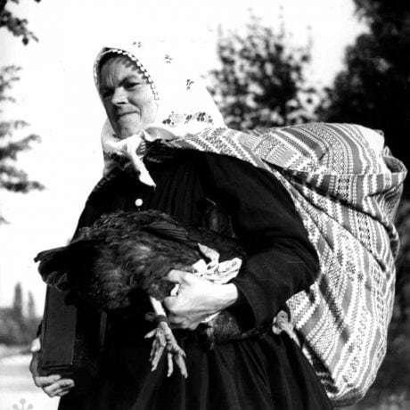 Kmotra nesie jedlo šestonedieľke. Dolný Lopašov (okr. Trnava), 1956. Archív negatívov Ústavu etnológie SAV Bratislava. Foto: V. Törey