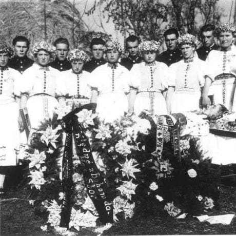 Dievčatá oblečené ako družice s vencami na hlavách a mládenci vo vojenských uniformách na pohrebe mládenca. Dačov Lom (okr. Veľký Krtíš)